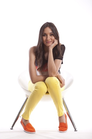 Full length of beautiful young teenager girl sitting in a chair photo