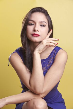 sexy latina model in a blue dress on a yellow background photo