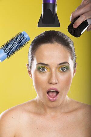 rubia ojos azules: Hermosa joven en el tratamiento de belleza completo. Maquillaje y peluquería. Aislado sobre fondo amarillo