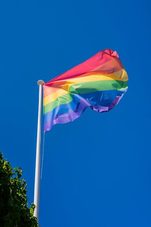 LGBT pride flag hung on a mast and waving in the blue sky