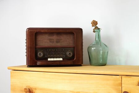 Vintage radio made of wood and green vase on a old table