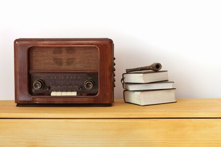 Vintage radio made of wood, old books, green vase and a pipe on a table