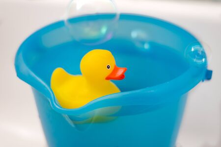 Yellow rubber duck in a blue bucket full of water and soap bubbles