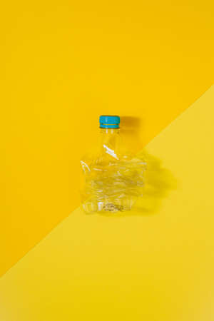 Vertical color image with an overhead view of a transparent and crushed plastic bottle with blue cap on a yellow background. Recycling and environment concept. Stock Photo