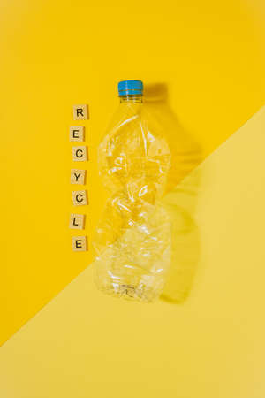 Vertical color image with an overhead view of a transparent and crushed plastic bottle with blue cap on a yellow background and the word recycle. Recycling and environment concept.