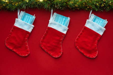 Horizontal color image with an overhead view of a christmas decoration with Coronavirus on a red background, christmas socks, face masks and hydroalcoholic gels. Covid concept on christmas.