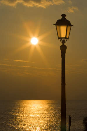 Sun reflected on the sea and streetlight at sunset
