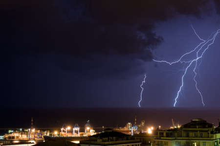 Lightning into the sea near the port of Genova, Italy during a violent storm Stock Photo