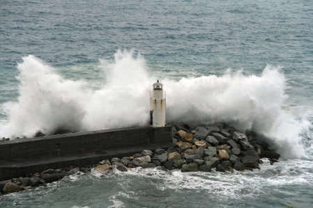 calving: waves break on the lighthouse at Camogli, Italy