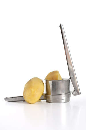 closeup of potato masher with two boiled potatoes isolated on white background photo