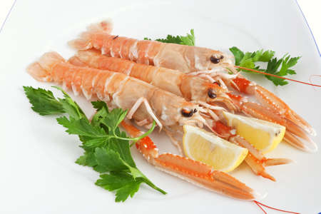 closeup of three prawns with parsleyand lemon on a white plate isolated on white background