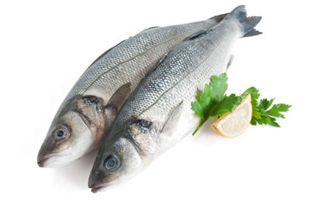 two sea bass with lemon and parsley isolated on white background photo