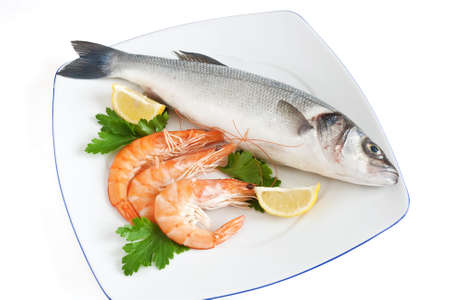 plate with sea bass, prawns, lemon and parsley isolated on white background photo