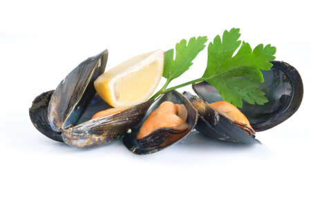 mediterranean cuisine: three mussels boiled with lemon and parsley isolated on white background Stock Photo