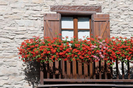 characteristic: characteristic alpine balcony with red and pink geranium flowers