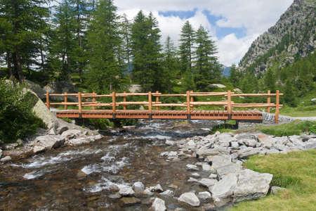 small bridge over an alpine creek in Arpy valley, Aosta, Italy Stock Photo - 8061076