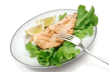 plate with grilled salmon trout, lettuce isolated on white photo