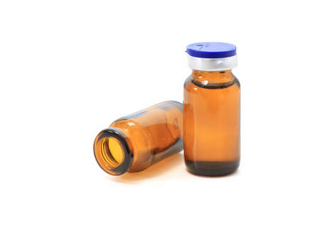 two glass bottles with medicine over white background photo