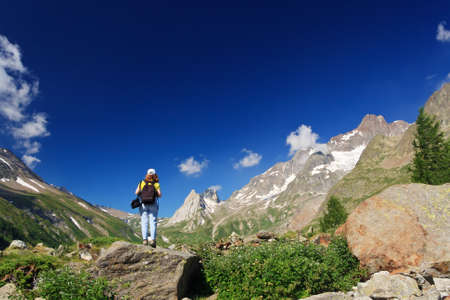 young woman stands on a rocks in Italian Alps