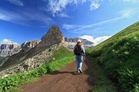 fassa: hiker walks on a path in Fassa Valley, Italian Dolomites Stock Photo