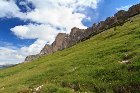 green slope beneath Catinaccio mountain, Italian Dolomites photo