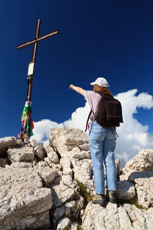 female hiker pointing the peak cross under deep blue sky Stock Photo - 13094662