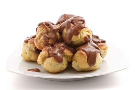 profiterole: profiteroles with chocolate sauce over white background Stock Photo