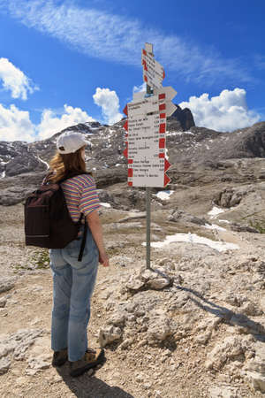 woman facing directions for trekking in Pale di San Martino mount, Italy photo