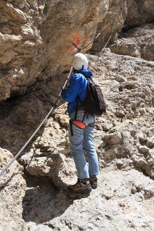 cir: female climber ascending rocks on via ferrata pathway Stock Photo