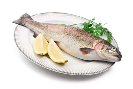 plate with rainbow trout, lemon, and parsley photo