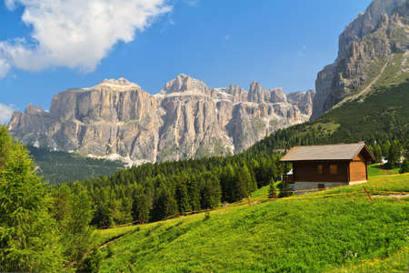 summer landscape in Fassa Valley with a small chalet beneath Dolomites mountains, Trentino, Italy Stock Photo
