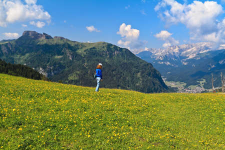 fassa: hiker on flowered meadow in Val di Fassa, Trentino, Italy - MR attached Stock Photo
