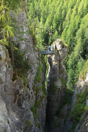 Monolith: woman on via ferrata Sass de rocia with a metal bridge on top of a monolith, Italian Dolomites