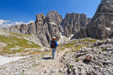 sella: hiker on footpath  in Sella mountain, on background Mezdi valley and Piz da Lech peak, south Tyrol, Italy Stock Photo
