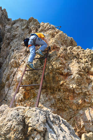 mountaineering: female climber on Cir V via ferrata, Gardena pass, Italy