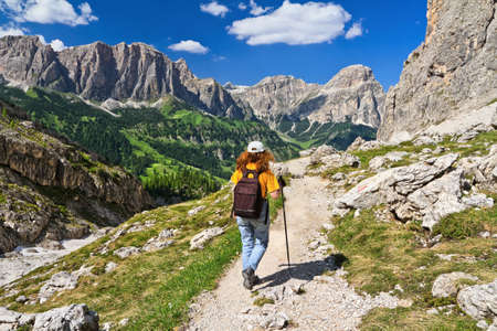 dolomites: hiker on footpath  in Sella mountain, on background Colfosco and Badia Valley, south Tyrol, Italy