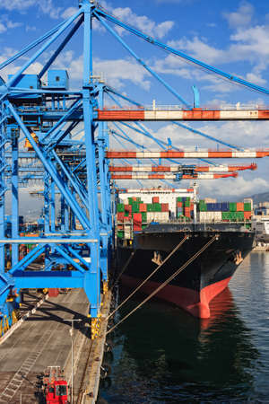 Cranes and ship in the container terminal, port of Genoa , Italy