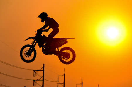 Practice day,silhouette of a motorcycle motocross jumping on sunset background. Reklamní fotografie