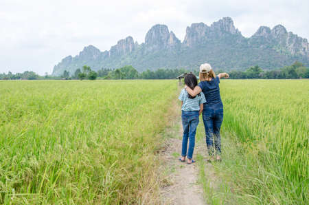 Mom points her daughter to see something in the rice fields,Nakhonsawan province in Thailand