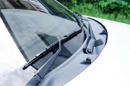 Sectie van de voorzijde van een wit voertuig en zijn voorruitbeschermkap en wissers. Stockfoto