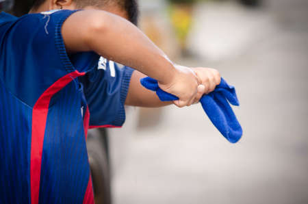 squeezing: The boy squeezed a wet blue towel from the water. Stock Photo