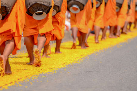 limosna: The monks are walking on yellow marigold petals.  The faithful Buddhists are placed for the monks.