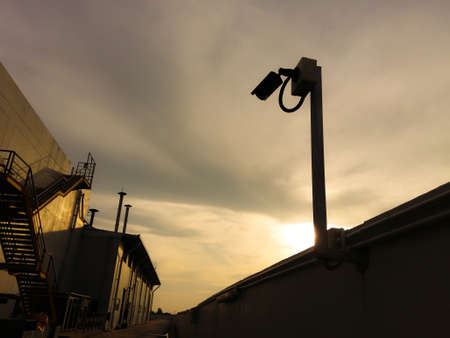 Security camera on the fence wall in the surveillance of industrial facilities.