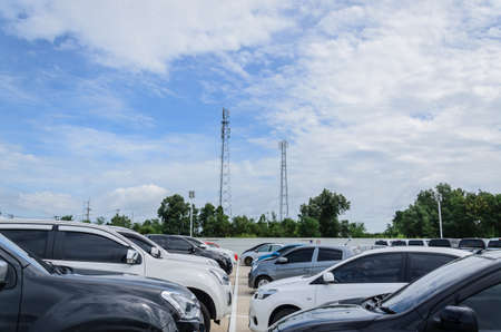 Many cars parked in the parking lot with blue sky background.