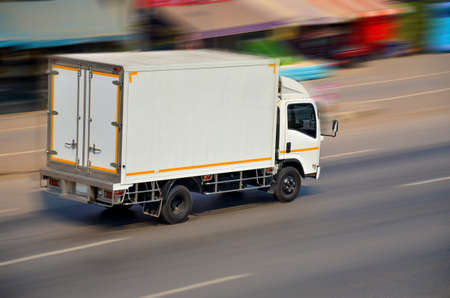 Motion image of the white truck driving with speed Stock Photo