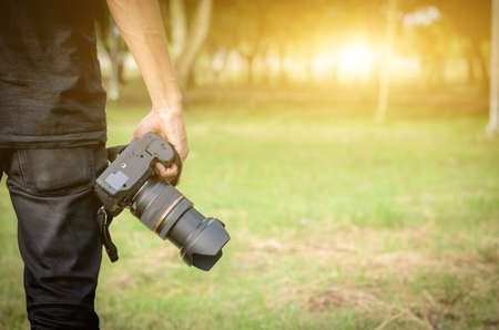 photographer holding a camera in his hand in the forest. Stock Photo