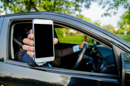 Young businessman lifted their smartphone in the car. Stockfoto