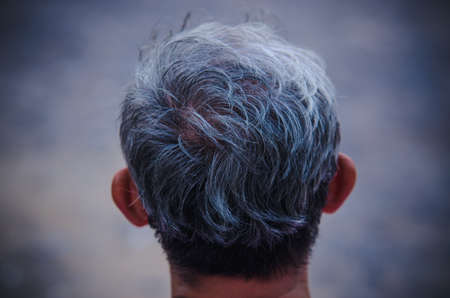 Photos from behind the gray haired man 版權商用圖片 - 148098129