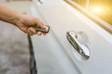 Car remote control by smart key, Hand holding smart key to lock doors of white car Reklamní fotografie