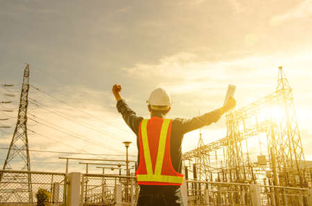 Electrician proudly raise their hands at the power substation against the sunrise background. Stock fotó
